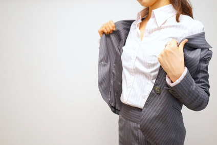 / Woman putting off her jacket in a office