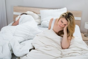 Woman On Bed While Man Sleeping In Bedroom